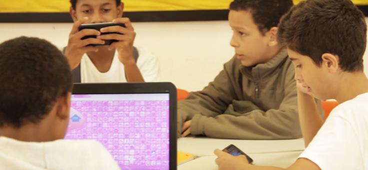 Quatro estudantes da escola municipal André Urani estão em volta de uma mesa utilizando computador e celulares