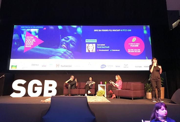 Três palestrantes dividem palco do festival Social Good Brasil. Há um intérprete de Libras, em pé
