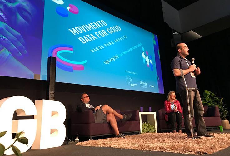 Américo Mattar, diretor presidente da Fundação Telefônica Brasil, está em pé, apoiado por muletas, no palco do festival Social Good Brasil
