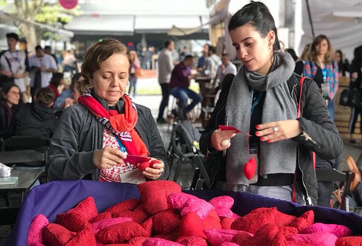 Duas mulheres pegam brindes do festival Social Good Brasil