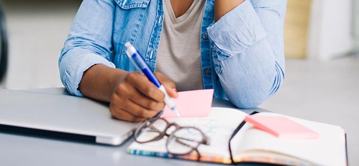 Na imagem é possível ver a silhueta de uma pessoa escrevendo termos sobre educação em um pedaço de papel. Há um par de óculos sobre a mesa