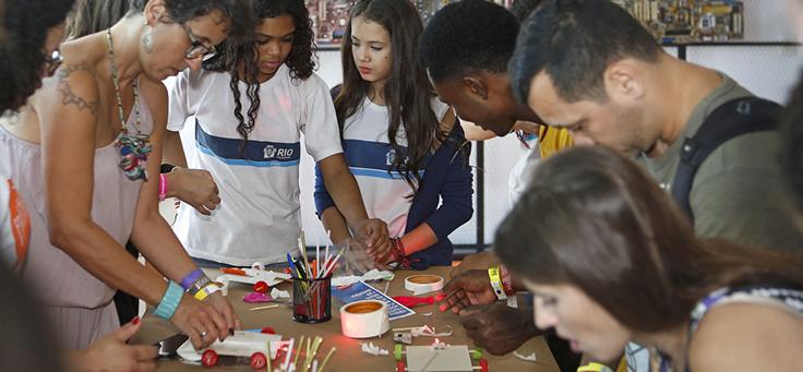 Cerca de 10 jovens rodeiam mesa enquanto constroem carrinho movido a bexiga em oficina do Programaê no Educação 360