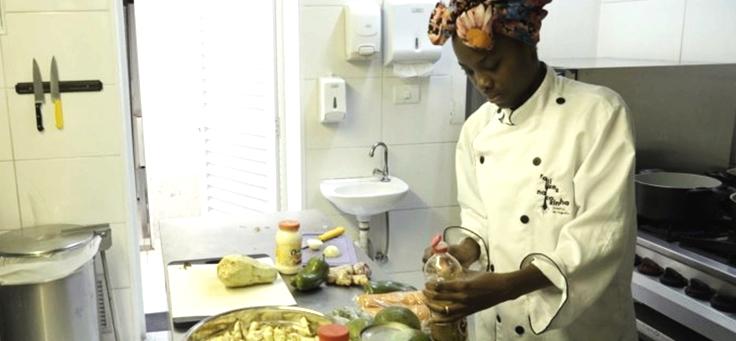 Jovem cozinha no espaço do Open Taste destaque de doc sobre empreendedorismo jovem. Ela está cortando alimentos e usa um turbante na cabeça