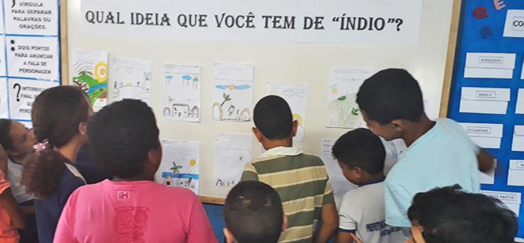 Na imagem alunos do professor Isaias olham para desenhos que mostram a visão deles sobre índios em etapa de projeto que alia leitura, tecnologia e pesquisa.