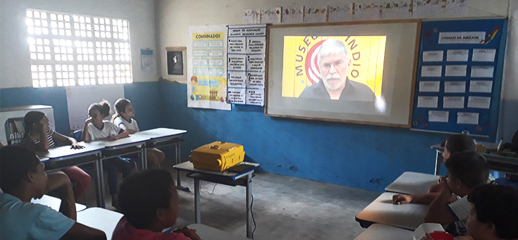 Na imagem alunos do professor Isaias estão sentados em roda em sala de aula, assistindo a vídeo em etapa de projeto que alia leitura, tecnologia e pesquisa.