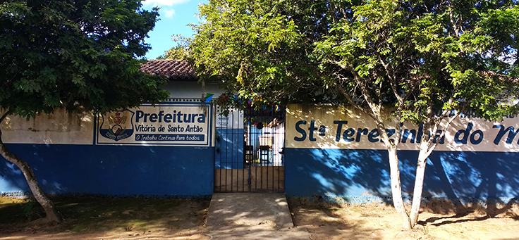 Imagem mostra muro azul e árvores em frente à Escola Municipal Santa Terezinha do Menino Jesus, onde professor criou projeto que alia leitura, tecnologia e pesquisa.