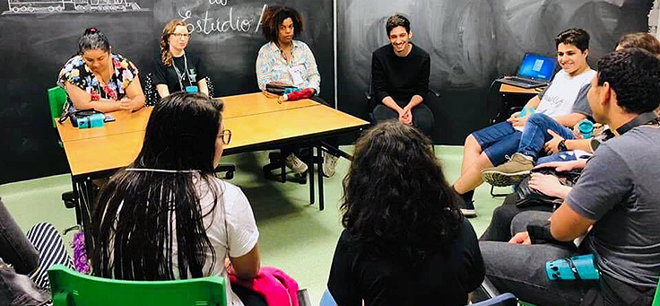 Dez professores estão sentados em roda durante atividade em mostra de boas práticas pedagógicas realizada em Viamão-RS.
