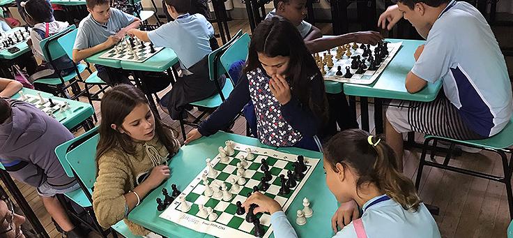 Em primeiro plano, duas jovens disputam partida de xadrez e uma terceira as observa em pé durante atividade em mostra de boas práticas pedagógicas realizada em Viamão-RS.