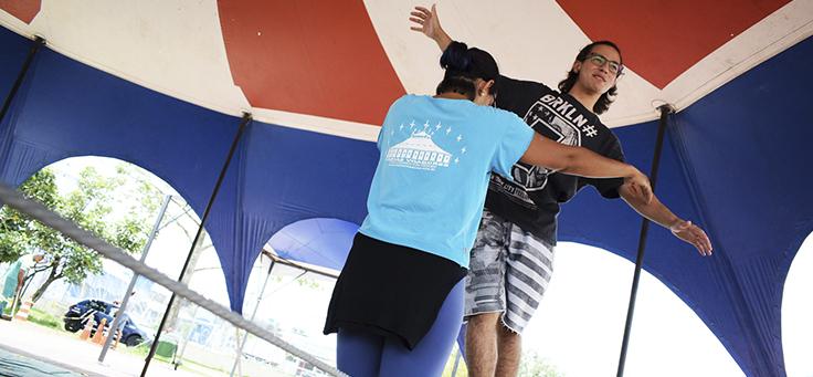 Instrutor ajuda aluno a caminhar na corda bamba em atividade do Cidade na Escola, que promove a educação integral