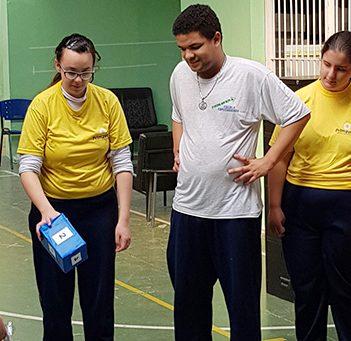 Na imagem, grupo de alunos da Escola Primavera estão em pé diante de uma espécie de tabuleiro desenhado com fita no chão durante dinâmica sobre programação