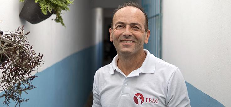 Valdeci Ferreira está posando para foto em corredor pintado com faixas brancas e azuis – matéria sobre como a luta dele por prisões humanizadas foi destaque em Voluntariado em 2018.
