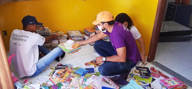 Na imagem, voluntário de causas sociais usa camiseta do Programa de Voluntariado da Fundação Telefônica Vivo e auxilia a arrumar livros.