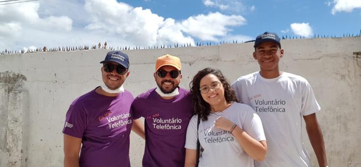 Sarlan Bernardo, que atua em diversas causas sociais, está posando ao lado de três colegas com camisetas do Dia dos Voluntários Telefônica.