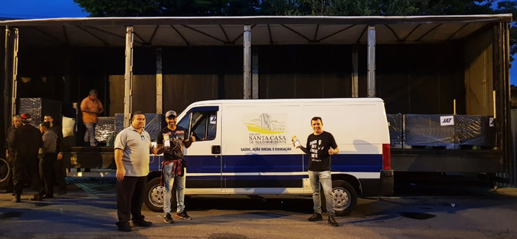 Tiago Elvis está posando em frente a van que transporta leites para Santa Casa de Belo Horizonte. O voluntário atua em diversas causas sociais.