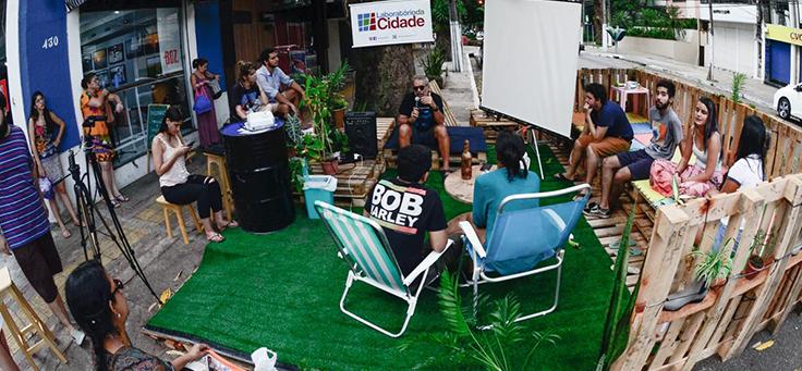 Pessoas estão sentadas em parklet montado pelo Laboratório da Cidade, um dos projetos que remodelam a relação entre cidades e pessoas.