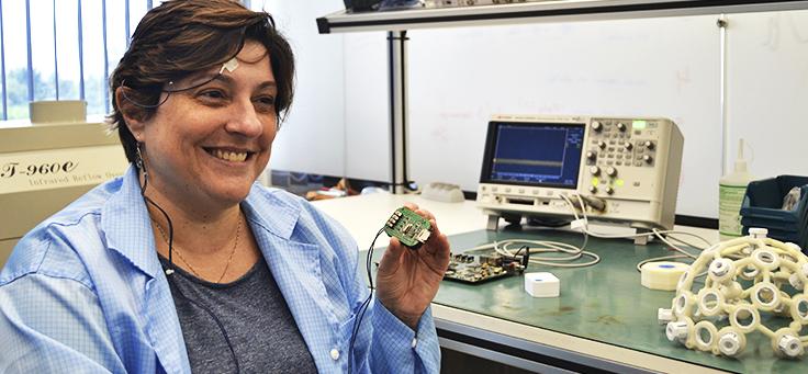Mulher usa dispositivo Epistemic e sorri para a foto – matéria sobre dispositivo que alerta sobre ataques epiléticos foi destaque em empreendedorismo social em 2018.