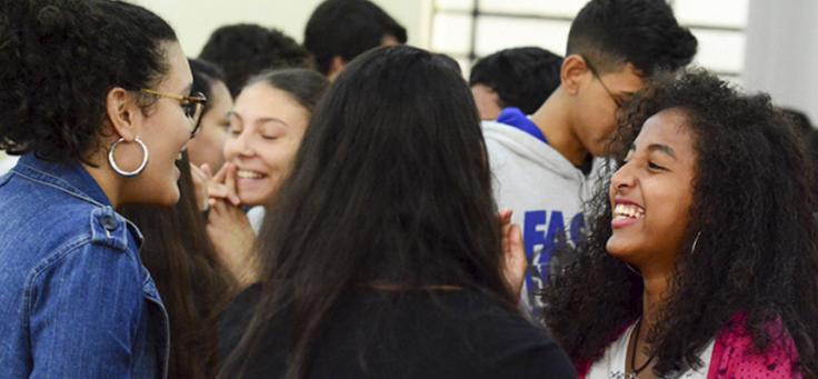 Grupo de jovens conversa, é possível ver em primeiro plano o rosto de uma menina de óculos e cabelos curtos e o de outra menina, de cabelos longos e crespos – matéria com jovens do Pense Grande foi destaque em empreendedorismo social em 2018.