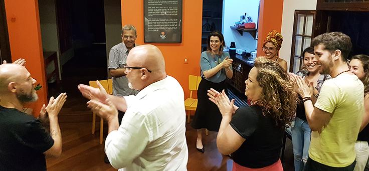 Participantes da roda de conversa sobre engajamento no evento Mobilizaí estão em pé formando roda e aplaudindo.