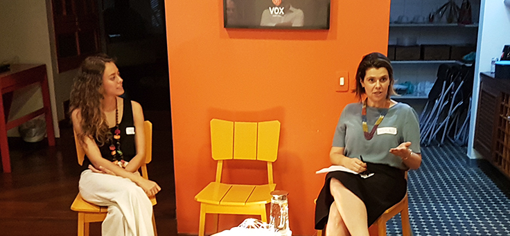 Mila Gonçalves, gerente de programas sociais da Fundação Telefônica Vivo está sentada em uma cadeira com as pernas cruzadas e falando sobre engajamento no evento Mobilizaí.