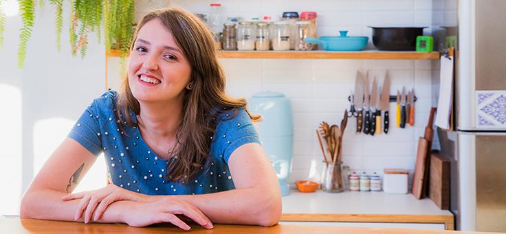 Cristal Muniz, autora do blog Um ano sem lixo, está com os braços cruzados sobre uma mesa e sorrindo para foto – matéria sobre como viver sem gerar lixo foi destaque em Voluntariado em 2018.