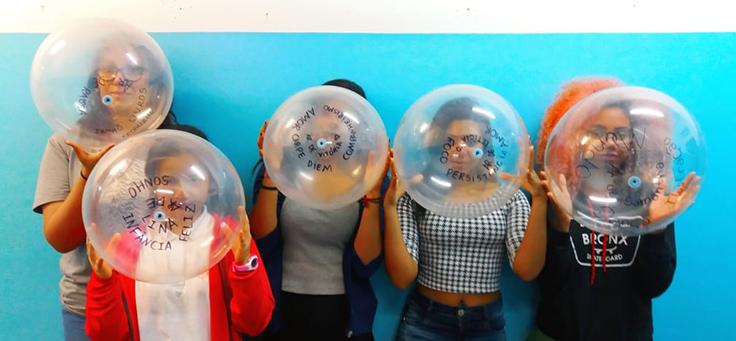 Encostados em uma parede, alunos seguram bolas de plástico transparente com alguns escritos.