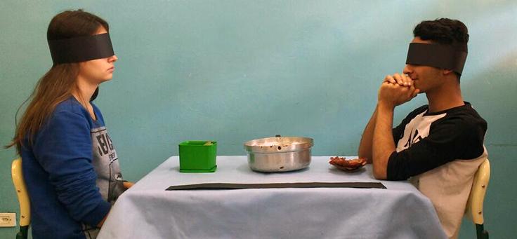 Dois alunos com vendas nos olhos estão sentados um frente ao outro em uma mesa com objetos expostos.