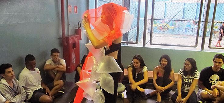 Alunos sentados no chão, observam performance de outra aluna que está de pé.