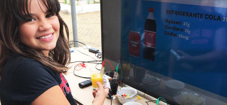Imagem mostra aluna em frente a um monitor que mostra informações nutricionais de um refrigerante