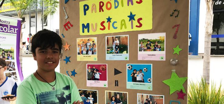 Imagem mostra aluno em frente ao painel interativo que reuniu paródias de músicas.
