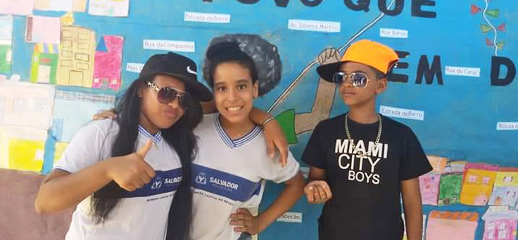 Alunos usando bonés e óculos escuros, em alusão à cultura hip hop, posam em Mostra que resgata culturas marginalizadas, no projeto É de Quebrada que Eu Vou.