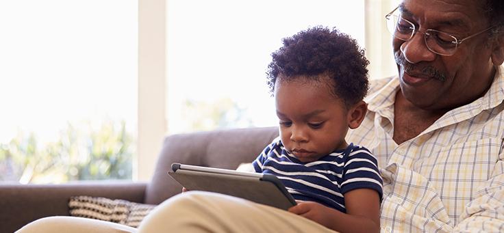 Na imagem, um idoso está com uma criança no colo, que segura um tablete nas mãos.