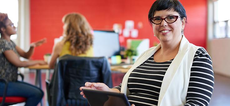 Na imagem, mulher de cabelos curtos e óculos sorri para a foto segurando um tablete nas mãos.