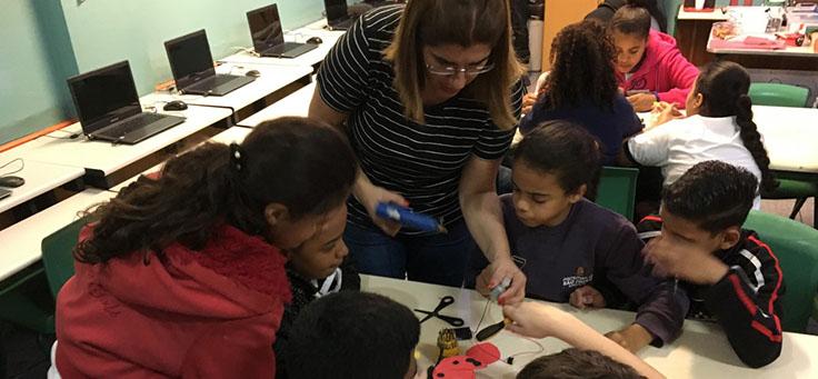 Professora Débora Garofalo, finalista do Nobel da Educação, está segurando pistola de cola quente para auxiliar alunos em oficina sobre robótica