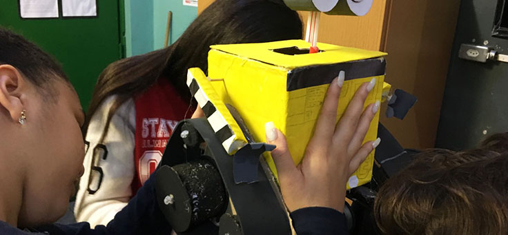Alunos estão colando a cabeça de um robô feito de sucata em aula da professora Débora Garofalo, finalista do Nobel da Educação.