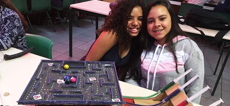 Duas alunas estão posando em frente a tabuleiro de jogo feito com sucata em aula sobre robótica da professora Débora Garofalo, finalista do Nobel da Educação.