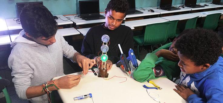 Três alunos estão segurando dispositivo que emite luz verde em aula de robótica da professora Débora Garofalo, finalista do Nobel da Educação.