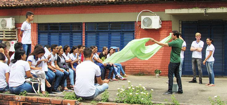 Professor Jayse Antonio, finalista do Nobel da Educação, estende pano verde em frente a seus alunos, que estão sentados em círculo no pátio da escola.