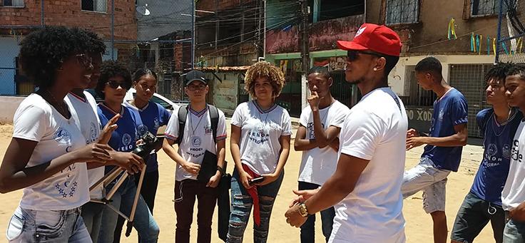 Alunos estão em volta do jogador Rogério Xodó, entrevistado em documentário descrito no e-book com práticas pedagógicas do CENOR, em campo do bairro Arenoso.