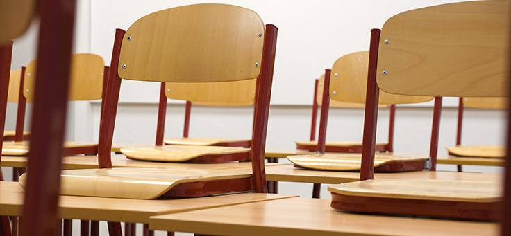 Na imagem, aparecem cadeiras escolares de madeira vazias em destaque.