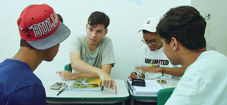 Quatro integrantes da chapa P.A.S. estão sentados em carteiras,, discutindo as propostas em cena do documentário Eleições, que traz protagonismo jovem aos cinemas.