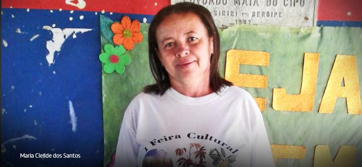 A professora Cleide posa para a foto atrás de um cartaz e usa uma camiseta que diz: Feira Cultural
