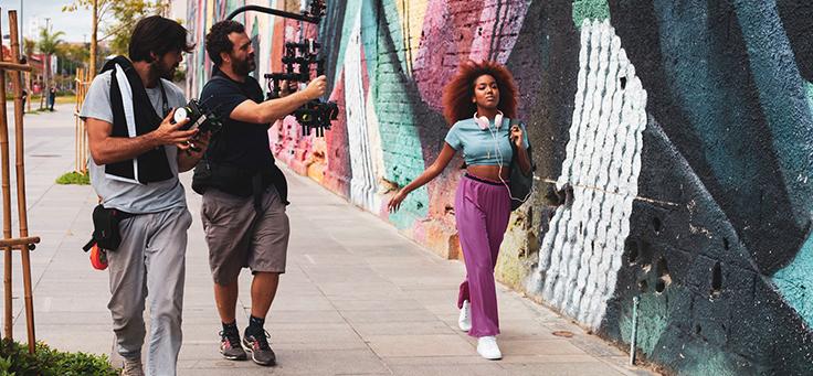 Na foto, a apresentadora Lellêzinha aparece caminhando na frente de um muro grafitado. Ela está sendo filmada por uma equipe de gravação
