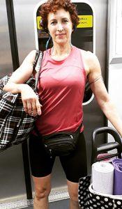 Sophia Bisilliat, uma das representantes de mulheres poderosas, está com uma bolsa grande pendurada no ombro e um carrinho com tapetes de ioga em um vagão de metrô em São Paulo.