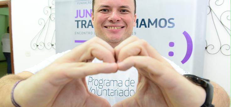 Voluntário do Grupo Telefônica está fazendo coração com a mão e usando camiseta do Programa de Voluntariado.