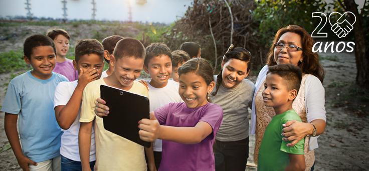 Imagem mostra crianças usando um tablete e representa ações descritas no Informe Social, que descreve atuação da Fundação Telefônica Vivo em comemoração de seus 20 anos.