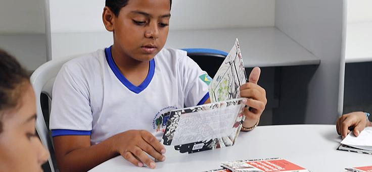 Menino vestindo uniforme escolar está sentando atrás de uma mesa lendo um livro