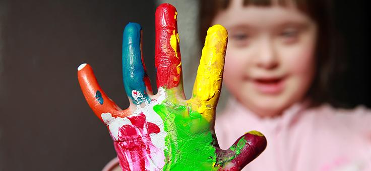 Criança com Síndrome de Down mostra mão com dedos pintados com tinta de várias cores em primeiro plano e tem seu rosto desfocado ao fundo.