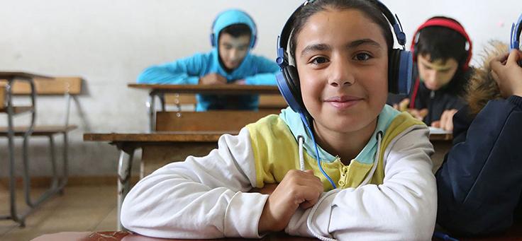 Menino usando moletom colorido e fone de ouvido faz parte do projeto Can't Wait to Learn, um dos premiados pelo uso de tecnologia da educação em iniciativa da Unesco.