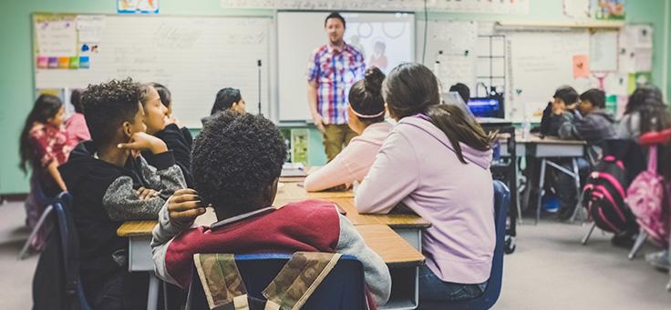 Alunos estão sentados em grupos e olhando para professor em sala de aula: valorização da carreira e formação continuada foram caminhos para melhorar a educação no Chile.