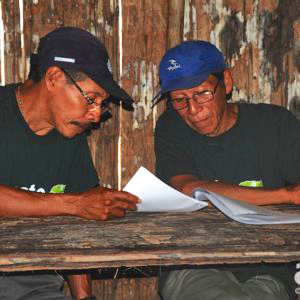 Dois xamãs da tribo Matsés dividem uma mesa e revisam enciclopédia medicinal, elaborada em parceria entre os indígenas e a ONG Acaté.